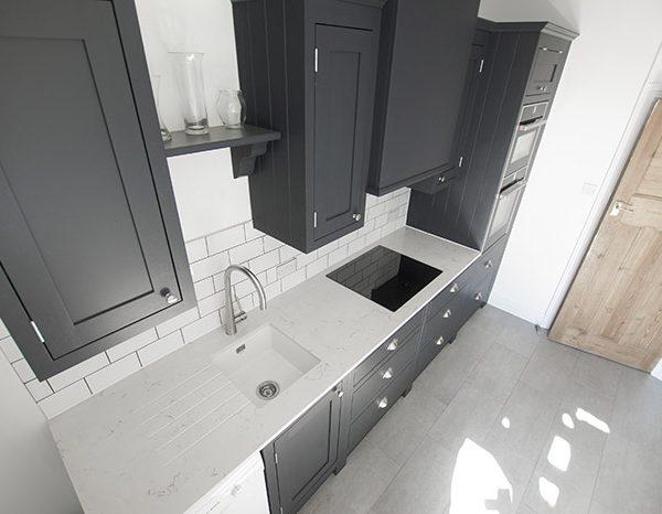 carrera quartz worktops installed in a dark blue kitchen